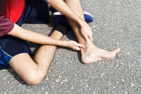 Sport man holding ankle in pain due to sprained ankle. Injury from workout concept