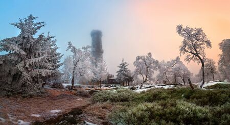 Amazing winter view of frosted trees and rock at sunrise, frozen lookout tower Sneznik, Bohemian Switzerland, the best photo