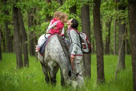 Girls enjoying horseback riding in the woods and kissing mother, young pretty girls with blond curly hair on a horse, freedom, joyful, outdoor, spring, healthy, happy hamily, kids on vacation forest