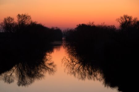 Beautiful sunrise in the Camargue national park. Rhone Delta, Provence, France, mirror reflection on water, trees reflecting on water, orange color, land of flamingos and wild horses