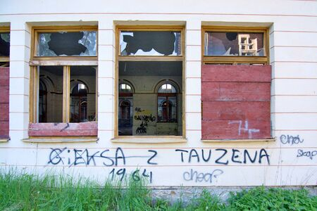 Devastated house with broken windows which are blinded by wooden boards