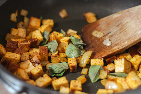 stiring: Helthy vegetarian dinner. Tofu with fried onion and oregano leaves in a frying pan. Stock Photo