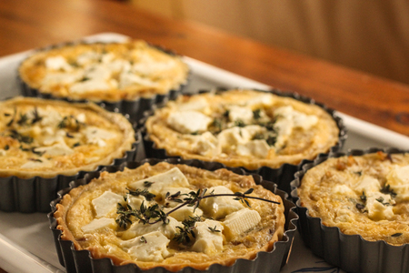 sprig: Delicious sheep cheese and onion tarts with a thyme sprig on top