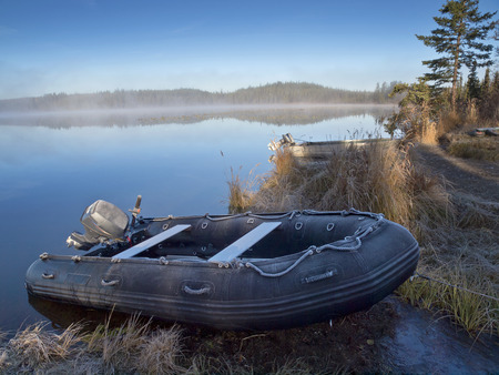 beached: Frosty inflatable boat beached onto the shore of Morchua Lake Stock Photo