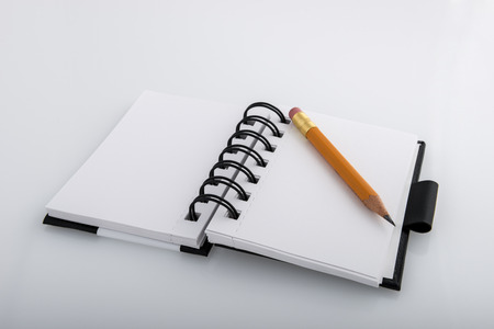 Open black and white ringed notepad and pencil resting on a white desk photo