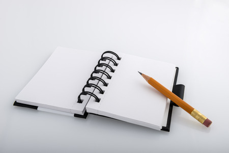 Open black and white ringed notepad and pencil resting on a white desk