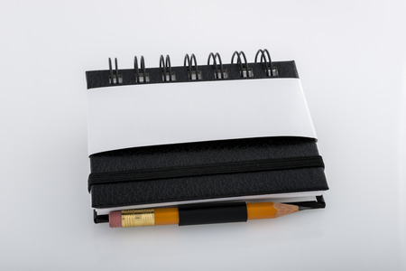 Black and white ringed notepad and pencil resting on a white desk