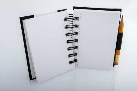 Standing open black and white ringed notepad and pencil resting on a white desk