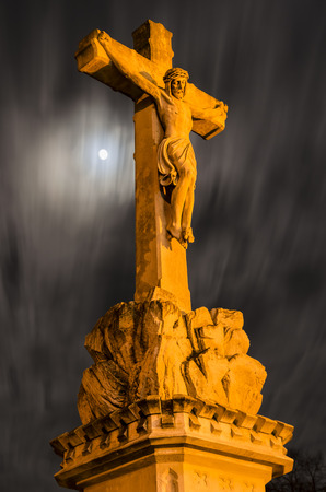 Illuminated statue of the crucified Jesus Christ on the night of the full moon
