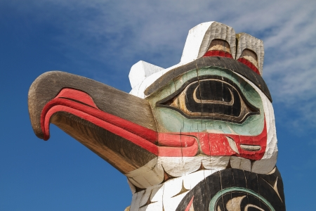 tlingit: Detail of totem pole in Alaska. Horizontal photo with blue sky in the background.  Stock Photo