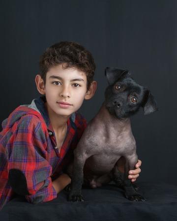 Portrait of boy and dog on black background photo
