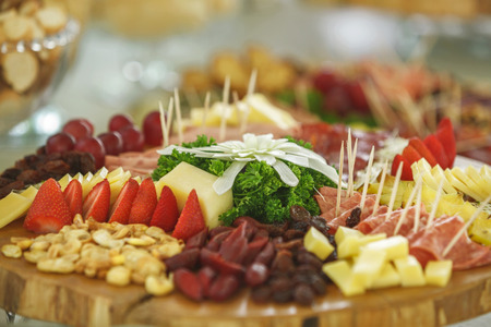 Catering service with various fruits and vegetables on wooden plate