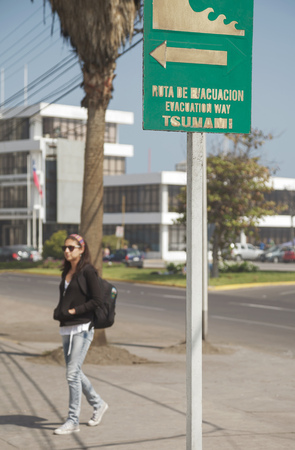 sign post: Woman following Tsunami Warning Sign in city of Iquique Chile.