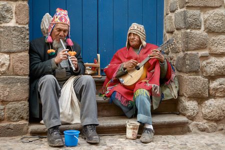 Two peruvian blind men with traditional clothes playing flute and mandoline in the street of Cusco, Peru 報道画像