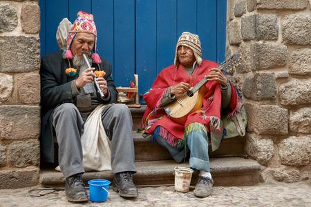 Zwei peruanisches blinde Männer mit traditioneller Kleidung spielt Flöte und Mandoline in der Straße von Cusco, Peru Standard-Bild - 58641908