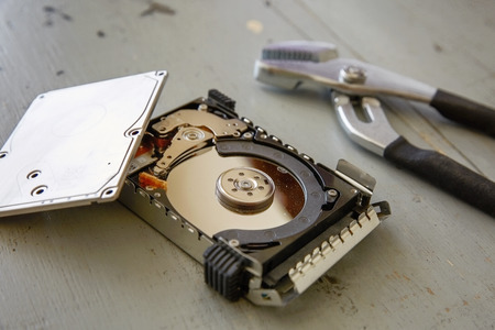 Broken and Destroyed Hard Drive Disk on Wooden Table. Stock Photo