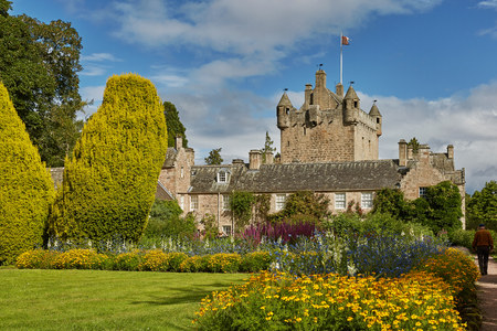 CAWDOR, NAIRN, SCOTLAND, UK - AUGUST 07, 2017: Front of Cawdor Castle with turret and drawbridge with bell and Stags Head Buckel Be Mindfull emblem. The castle has been known from Shakespeares tragedy Macbeth