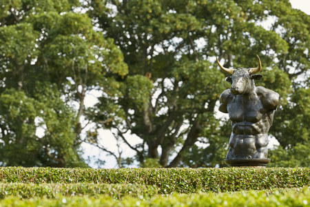 CAWDOR, NAIRN, SCOTLAND, UK - AUGUST 07, 2017: Labyrinth maze of Holly hedges in the Walled Garden of Cawdor Castle with bronze minotaur sculpture