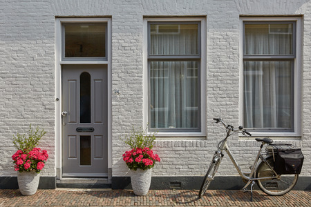 VLISSINGEN, NETHERLANDS - JUNE 15, 2017: House entrance decorated with flowers. Rustic style concept. Beautiful design elements of unknown building in Vlissengen Netherlands. Redactioneel