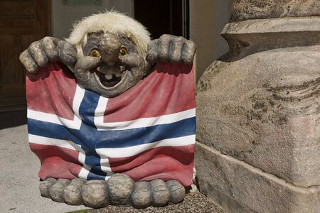 ALESUND, NORWAY - MAY 29, 2017: Troll figure holding a flag in front of a souvenir shop in Alesund, Norway. Troll is a class of being in Norse mythology and Scandinavian folklore. Sajtókép