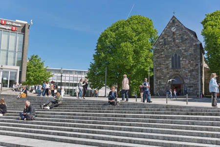 STAVANGER, NORWAY - JUNE 01, 2017: People relaxing and sitting on stairs in front of Stavanger Cathedral in Stavanger Norway. Sajtókép