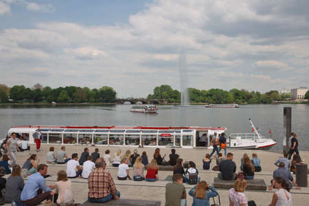 Hamburg, Germany - May 22, 2017: People enjoying summer day by Binnenalster Lake in Hamburg. With 1.7 million people Hamburg is the 2nd largest city in Germany.