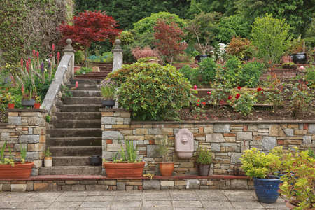 Natural stone steps and retaining wall, planter and garden border framing home entrance. Beautiful hardscape, colorful landscape design. Stock fotó