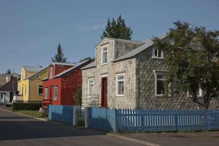 Traditional colourful houses covered in stone tiles or corrugated iron in the old part of Akureyri, Iceland. Stock Photo