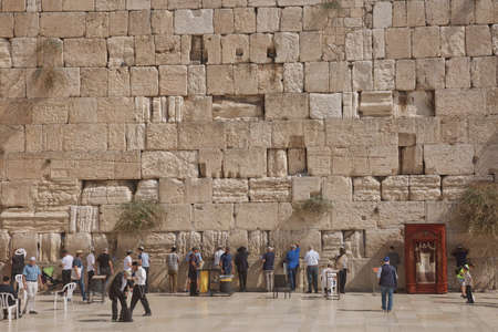 Jerusalem, Israel - October 23, 2017: People praying at the Western 'Wailing' Wall of Ancient Temple in Jerusalem. The Wall is the most sacred place for all jews in the world.
