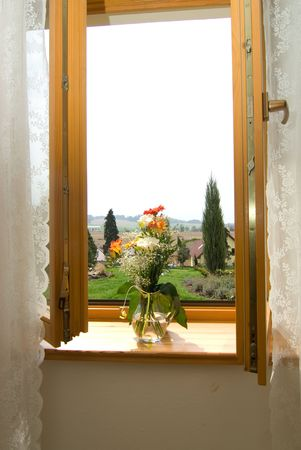 opened wooden window with bunch of flowers in jug photo