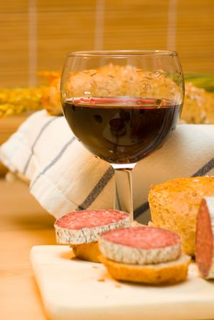 captivation: still life with red wine,sausage and bread roll Stock Photo