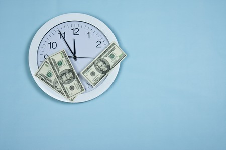 clock and money on blue background photo