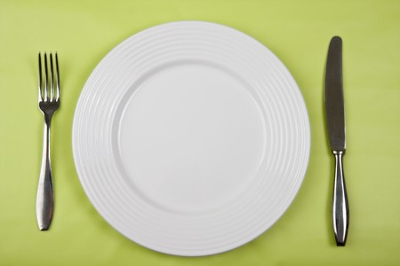 plate with knife and fork on green background Stock Photo - 4153936