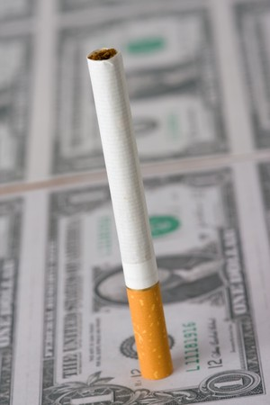 the cigarette laying on american money photo