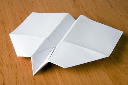 white paper plane on table photo