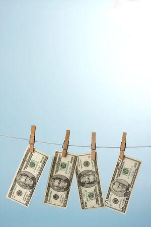 dollars hanging on line on blue background Stock Photo - 5086984