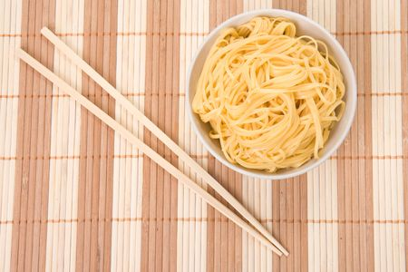 chopsticks,bowl and noodles on table photo