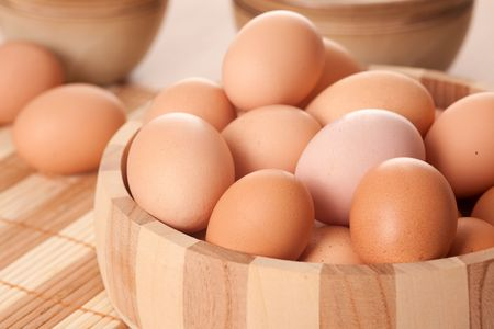 eggs in wooden bowl on table Stock Photo