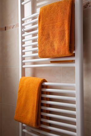 hotel bathroom: orange towels on heater in bathroom Stock Photo