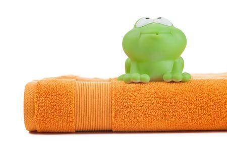 orange washcloth: orange towel and toy frog on white background