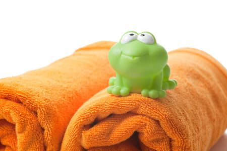 orange towels and toy frog on white background photo