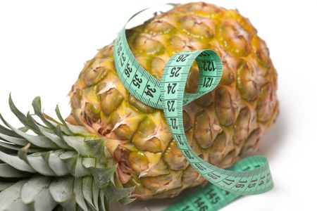 pineapple with measuring tape isolated over white photo
