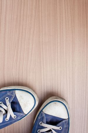 pair of blue sneakers on wooden floor Stock Photo