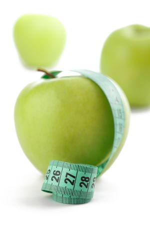 the green apple with measuring tape on white background photo