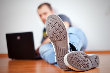 the man working with computer on wooden floor.  view on outsole Stock Photo - 6271876