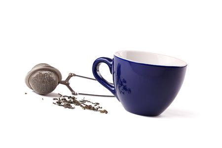 green tea , tea strainer and cup on white background photo