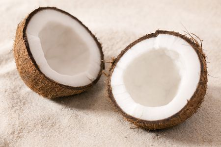 two half coconut lying in sand photo
