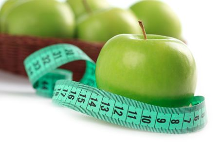 green apple and measuring tape on white background photo