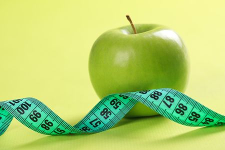 green apple and measuring tape on color background photo