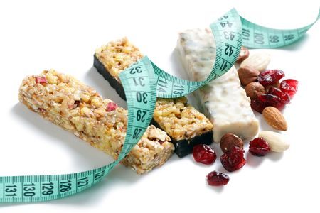 muesli bars with measuring tape on white background photo